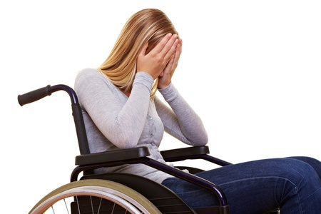 paraplegic: Young sad disabled woman in wheelchair crying