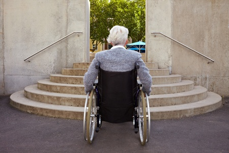 handicapped accessible: Elderly woman in wheelchair looking at stairs Stock Photo