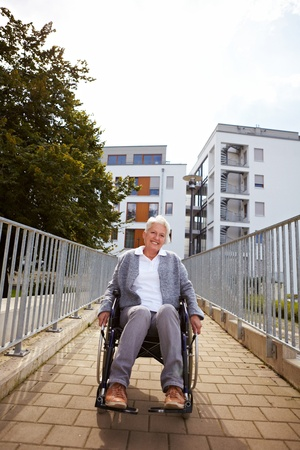 on ramp: Happy elderly woman in wheelchair using a ramp Stock Photo