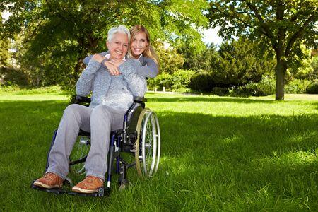 Femme heureuse en fauteuil roulant avec la jeune femme dans la nature Banque d'images