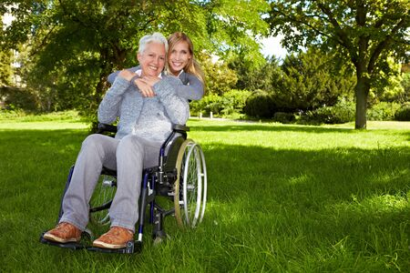 Happy woman in wheelchair with young woman in nature Stock Photo