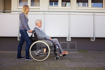 Elderly woman in wheelchair with nurse in urban setting photo