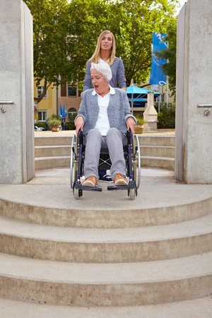 Elderly woman in wheelchair looking at inaccessible staircase Stock Photo - 8291451