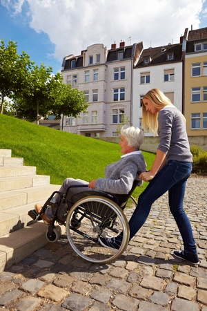 paralyzed: Young woman helping an elderly woman in wheelchair Stock Photo