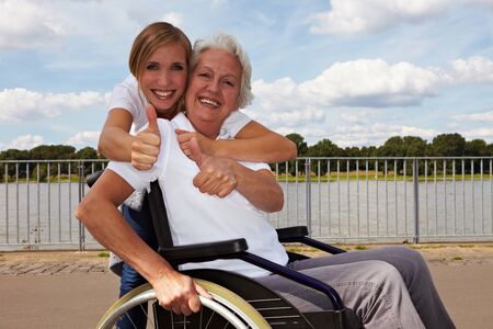 paralyzed: Happy disabled woman and nurse holding their thumbs up
