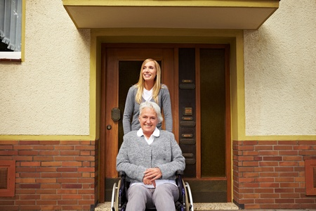 Smiling elderly woman in front of a retirement home photo