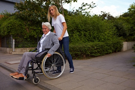 Young woman helping elderly woman in wheelchair over a curbstone photo