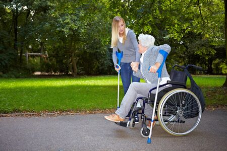 mobility nursing: Nurse helping elderly woman from her wheelchair onto crutches Stock Photo