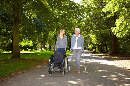 crutches: Nurse helping elderly woman with her physiotherapy outdoors