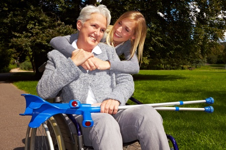 crutches: Happy grandmother in wheelchair with her grandchild in a park