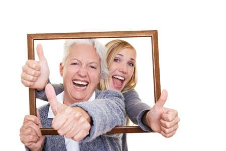 Grand-m�re et petite-fille regardant � travers un cadre vide Banque d'images