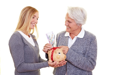 Grandmother putting money in piggy bank of her granddaughter photo