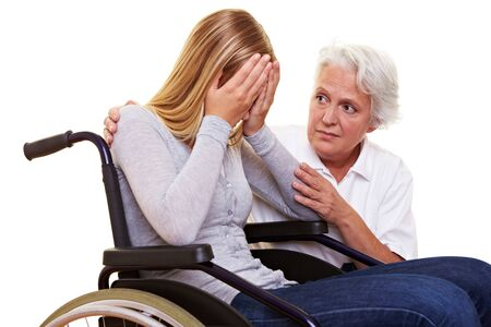 Nurse comforting young crying woman in wheelchair photo