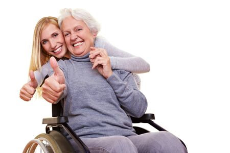 elderly care: Happy woman in wheelchair with granddaughter holding her thumbs up