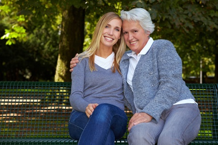 Young blonde woman sitting with her grandmother on a park bench photo