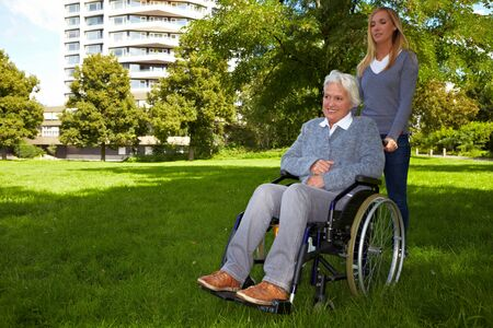 Happy woman in wheelchair with young woman in nature photo
