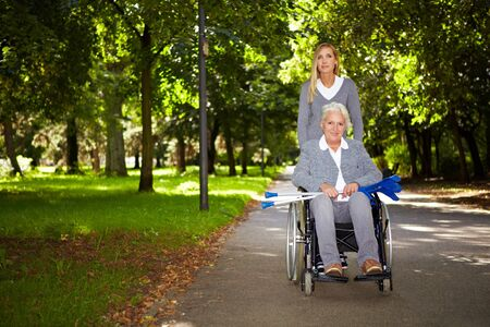 Happy woman in wheelchair with nurse in nature photo