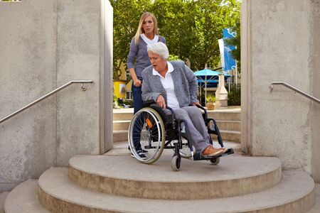 Elderly woman in wheelchair looking at inaccessible staircase photo
