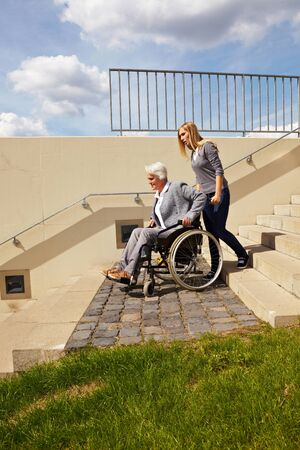 immobility: Young woman helping an elderly woman in wheelchair with staircase
