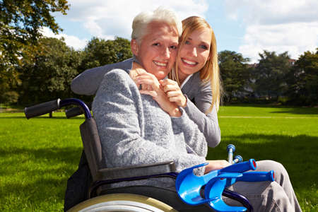 persona en silla de ruedas: Abuela feliz en silla de ruedas con su nieta en un parque