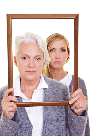 seriousness: Grandmother and granddaughter looking seriously through an empty frame Stock Photo