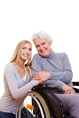 mobility nursing: Happy woman sitting in wheelchair with young nurse to her side