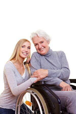 discapacitados: Mujer feliz sentado en silla de ruedas con la joven enfermera a su lado