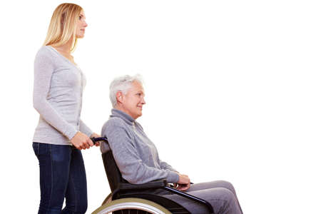 Young geriatric nurse driving elderly woman in wheelchair Stock Photo - 8347321