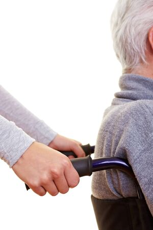 nursing home: Hands pushing elderly person in a wheelchair Stock Photo