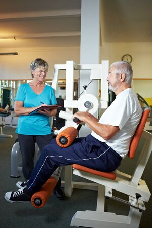 Female trainer talking with senior in gym Stock Photo - 8347369