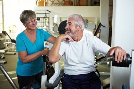 rehab: Two senior people talking in a gym