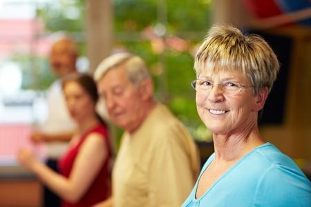 retirees: Senior woman doing aerobics in a gym