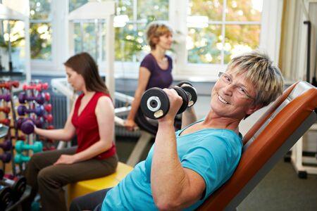 lifting weights: Mujeres superiores en un gimnasio de levantamiento de pesas Foto de archivo