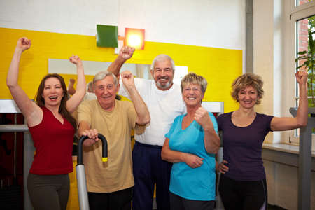 sport celebration: Mixed group with elderly people in a gym cheering