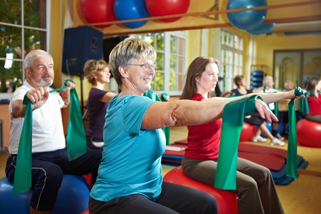 People in gym exercising with latex band Stock Photo - 8347356