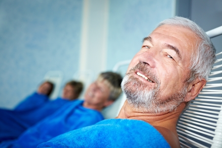 Elderly man and other people in relaxation room photo