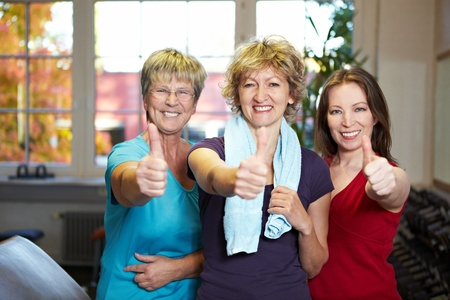 seniors laughing: Tre donne felice holding thumbs up in palestra Archivio Fotografico