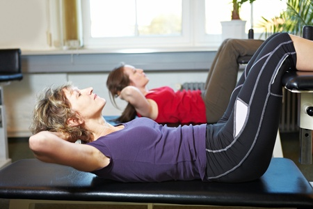 Two women doing sit-ups in a gym Stock Photo - 8347348