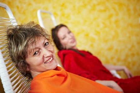 Two smiling women in relaxation room after spa treatment photo