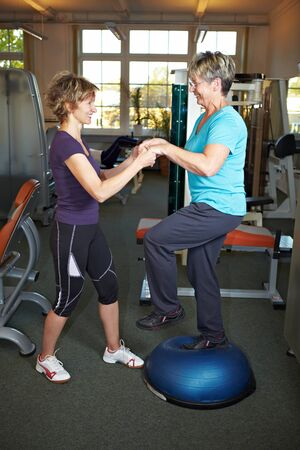 rehab: Woman helping with balancing exercises in gym