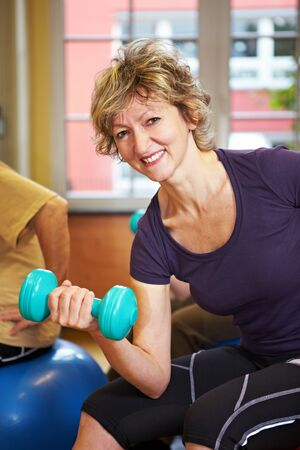 Smiling woman lifting dumbbell in a gym Stock Photo - 8347366