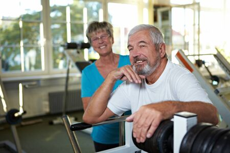 Two happy senior people together in a gym photo