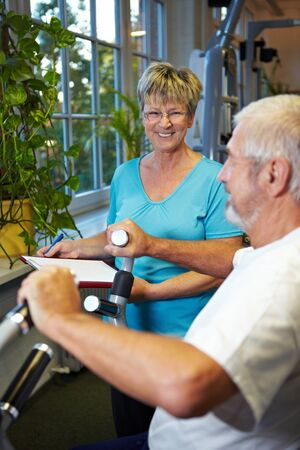 Man in gym using a rowing machine photo