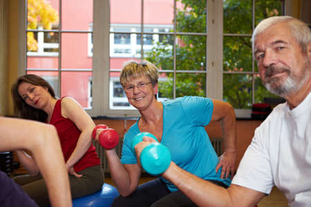 Group working out with dumbbells in gym photo