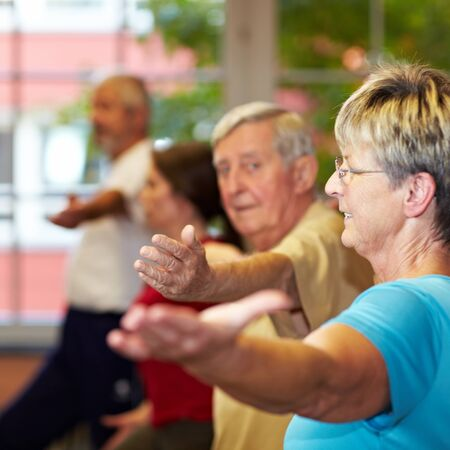 Senior woman in group doing aerobics in a gym photo