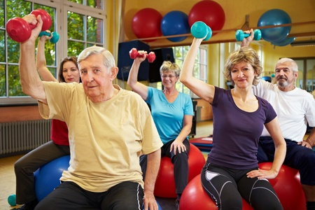 old train: Group working out with dumbbells in gym Stock Photo