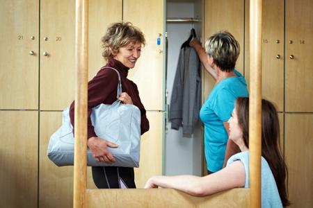 gym dress: Three happy woman chatting in locker room