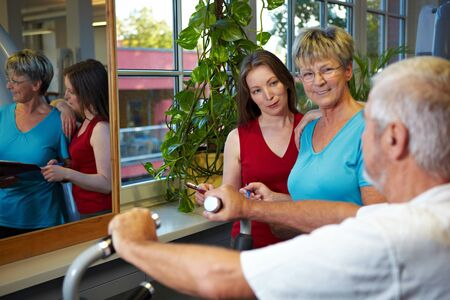 Elderly man in gym talking to two women photo