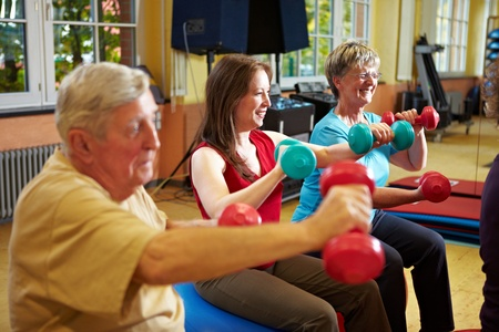 rehab: Group working out with dumbbells in gym Stock Photo