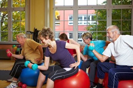 senior citizens: Group working out with dumbbells in gym Stock Photo